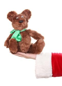 白い表面で隔離のおもちゃのクマを持っているサンタクロースの手