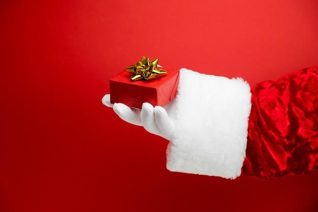 레드에 황금 활과 빨간 선물 상자와 산타 클로스 손