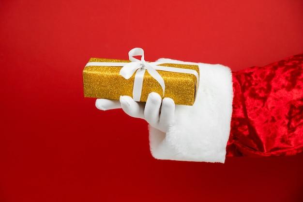 레드에 빛나는 황금 선물 상자와 산타 클로스 손
