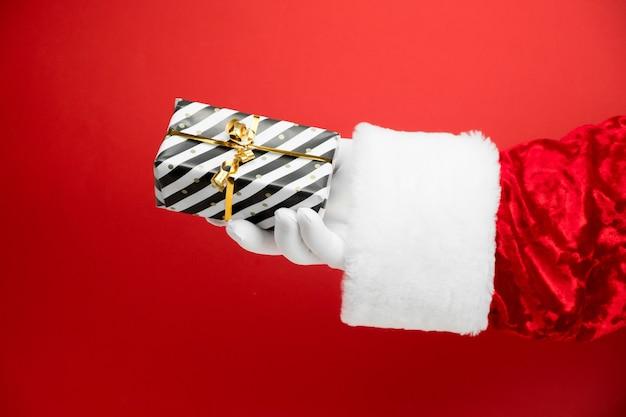 빨간색 줄무늬 선물 상자 산타 클로스 손