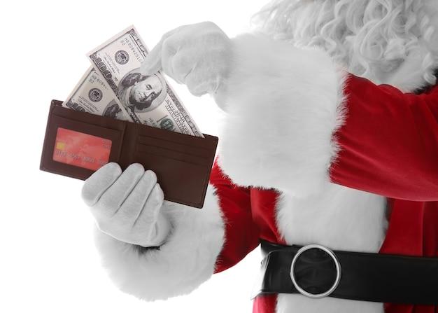 白い表面にお金とクレジットカードで財布を持っているサンタクロースの手