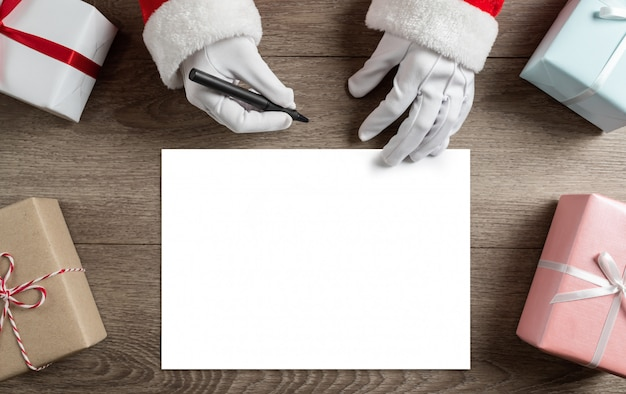 Santa claus hands is writing to do list and goals in a blank paper sheet