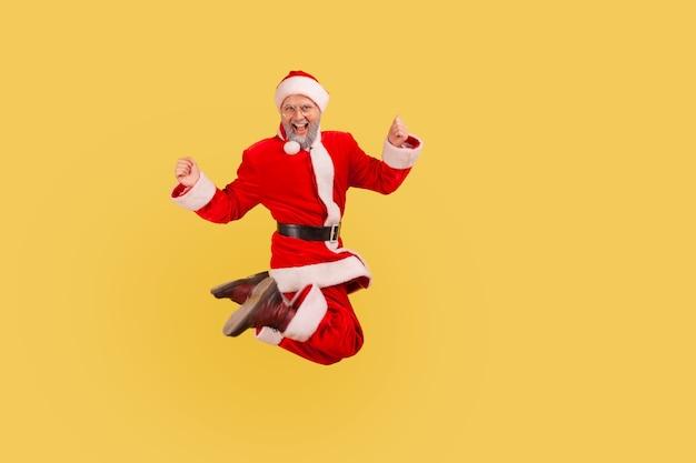 Santa claus has happy positive mood, jumping high and screaming, celebrating new year.
