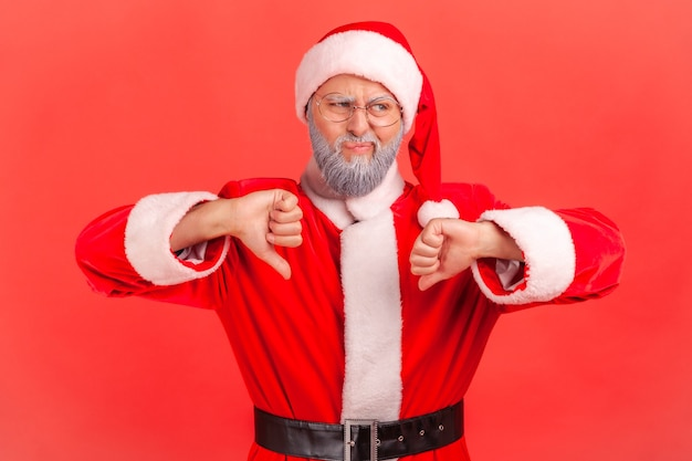 Santa claus has naughty expression and showing thumbs down, expressing disapproval