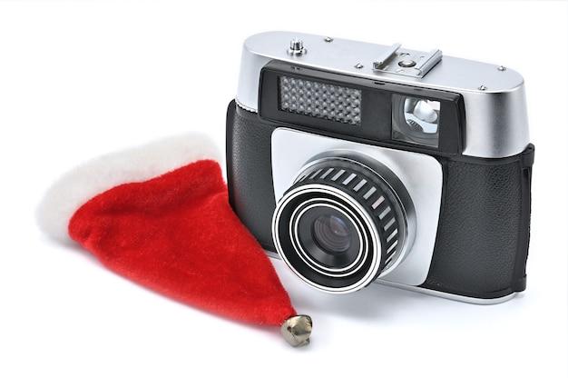 白い背景で撮影するためのサンタクロースの帽子とビンテージカメラ
