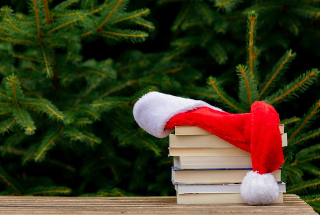 Santa claus hat and books on wooden table with spruce branches on background