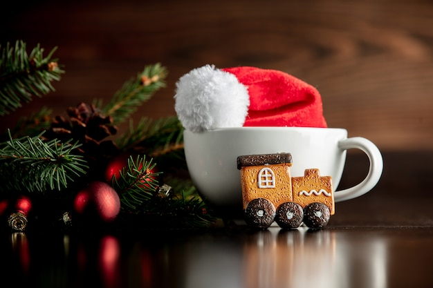 Santa claus hat and cup with gingerbread cookie