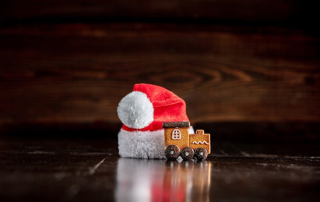 Santa claus hat and gingerbread cookie on wooden table