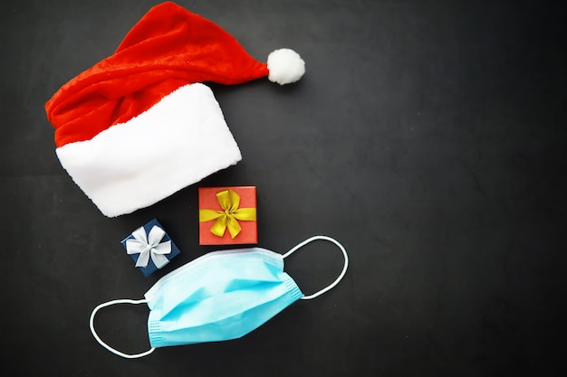 빨간 배경에 얼굴 마스크가 달린 산타클로스 모자, 안경, 코. 크리스마스 또는 새 해 축 하 개념입니다. 보호용 안면 마스크와 장식으로 만든 크리스마스 순록입니다. 건강 관리 개념입니다.