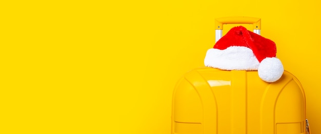 Santa claus hat lies on top of a yellow suitcase on a yellow background. banner.