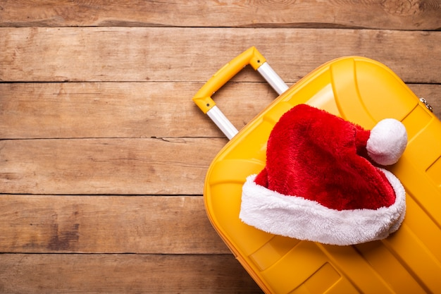 Santa claus hat lies on a yellow suitcase on a wooden background. top view, flat lay.