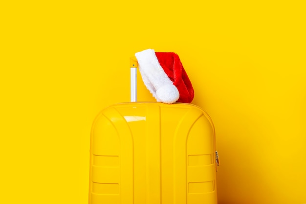 Santa claus hat lies on a yellow suitcase on a yellow background.