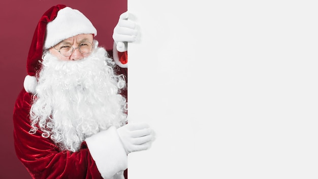 Santa claus in hat looking out of white wall