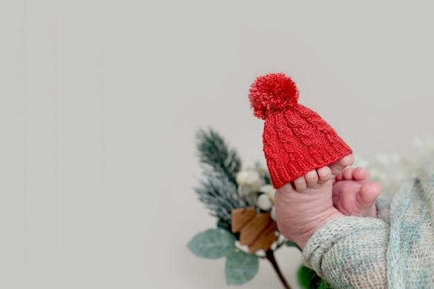 Шляпа санта-клауса. ножки новорожденного с рождественскими украшениями.