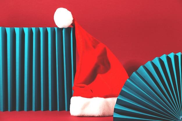 Шляпа санта-клауса на минималистичной ретро-сцене с геометрическими фигурами морского цвета на красном фоне