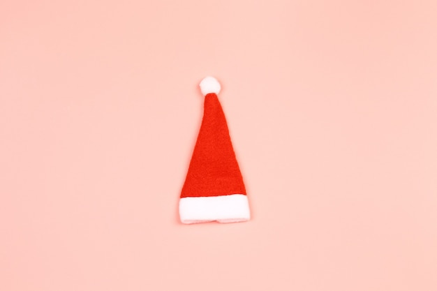 Santa claus hat on a pink background. minimalistic christmas scandy background with empty place for text