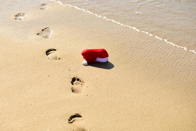 Santa claus hat on sea beach. christmas vacation. new year summer concept.