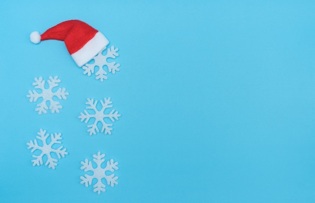 Santa claus hat and snowflakes on pastel blue background. minimal winter concept. christmas greeting card