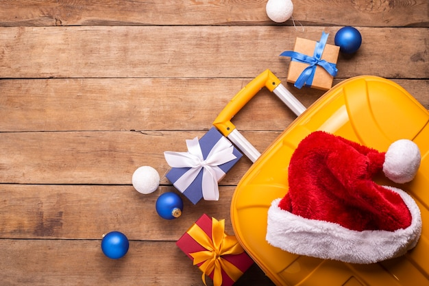 Santa claus hat, suitcase, gifts on a wooden background. top view, flat lay.
