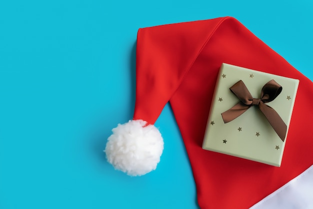 Santa claus hat with gift box on blue background, for mockup or design, place for copyspace