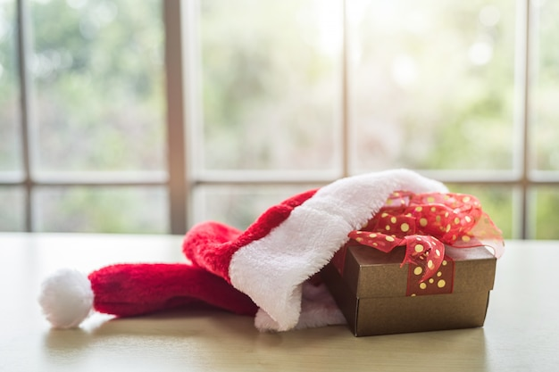 Шляпа санта-клауса с подарочными коробками, помещенными на деревянный стол интерьер комнаты, вид через окно с деревом фон с копией пространства, украшения во время рождества и нового года.