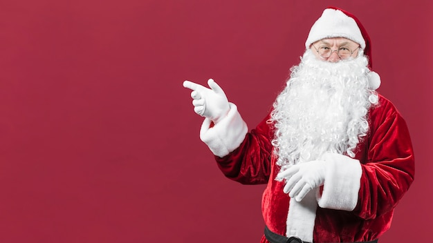 Santa claus in hat with pointing hand