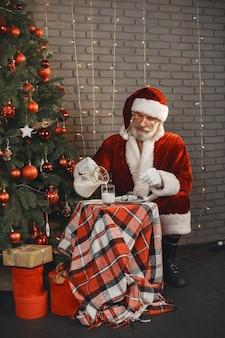 Дед мороз отдыхает у новогодней елки. украшение дома. подарок деду морозу.