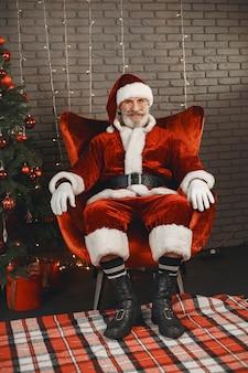 Дед мороз отдыхает у новогодней елки. украшение дома.