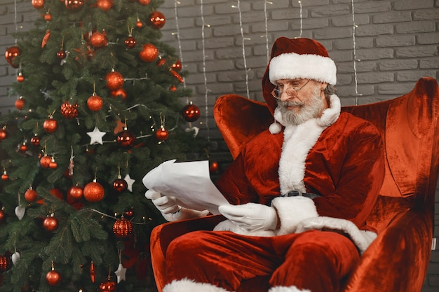 Santa claus having a rest by the christmas tree. home decoration. santa with letter from children.