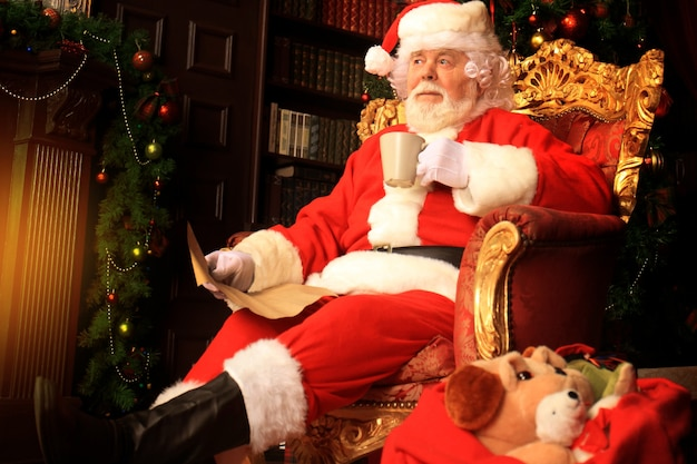 Santa claus having a rest in a comfortable chair near the fireplace at home.