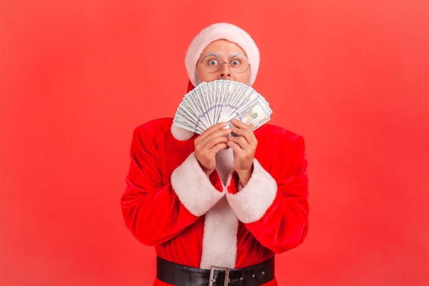 Santa claus hiding face with fan of dollars banknotes, winning big sum of money.