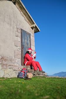 Путешественник санта-клауса с помощью телефона, сидя на лестнице дома в горах
