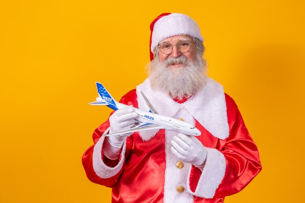 Санта-клаус держит маленький игрушечный самолетик на желтом фоне. рождественские путешествия концепция