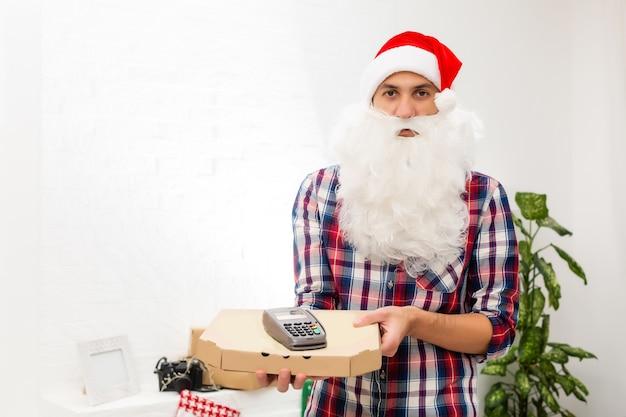 Санта-клаус держит коробку для пиццы и pos-терминал на белом фоне