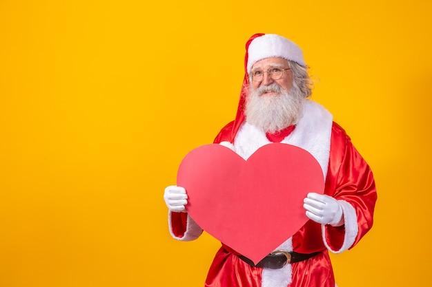 노란색 배경에서 큰 붉은 심장 카드를 들고 산타 클로스. 낭만적인 산타 클로스입니다.
