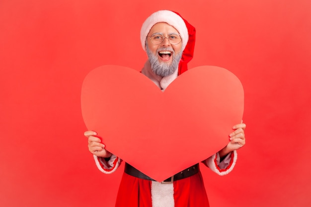 Santa claus holding big red heart in hands, looking at camera with excited expression.