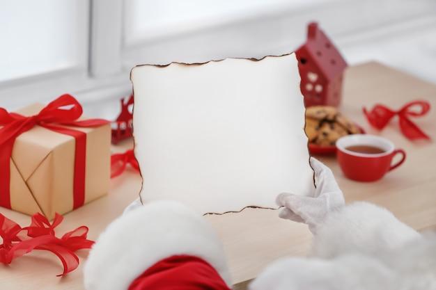 Санта-клаус держит чистый лист бумаги за столом