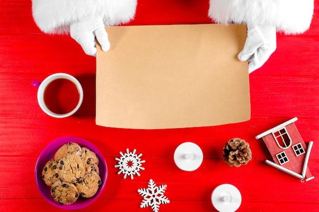 빨간색 배경에 빈 종이를 들고 산타 클로스