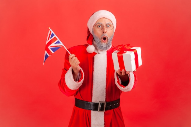 Santa claus holding british flag and wrapped present box, keeps mouth open.