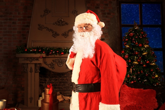 Santa claus holding carrying sack with gifts for kids.
