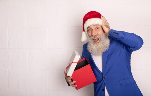 サンタクロースがクリスマスプレゼントを開催します。赤い帽子のひげを生やした年配の男性。クリスマス。新年。