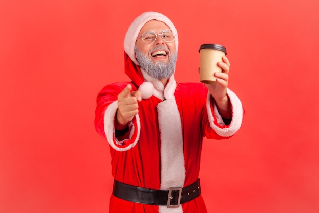 Santa claus holding coffee to go in hands and pointing to camera, smiling happily.