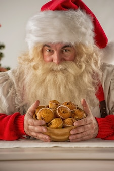 Santa claus holding cookie or cupcake at home