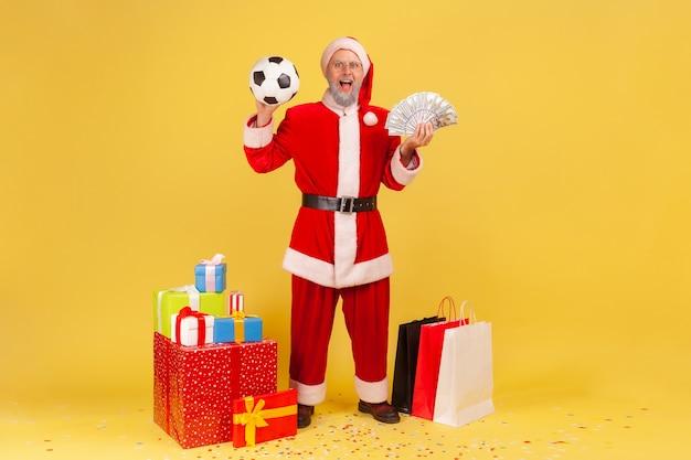 ドル紙幣を持っているサンタクロース、賭けから勝ち、クリスマスプレゼントを買う。