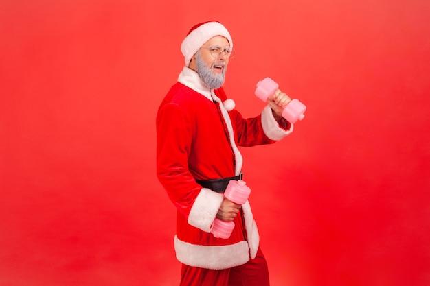 아령을 들고 팔을 훈련하고 흥분으로 카메라를 바라보는 산타클로스.