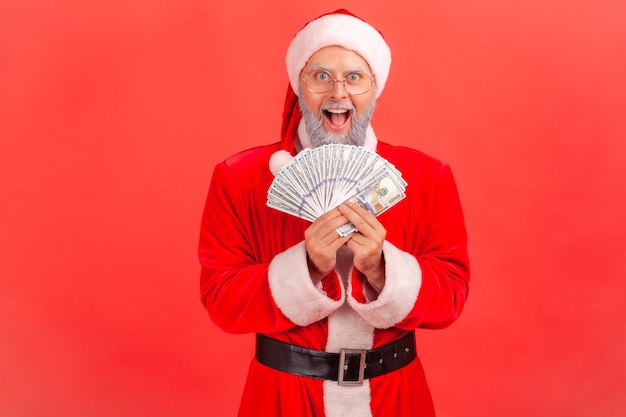 Santa claus holding fan of dollars, looking at camera with open mouth, excited to win big sum.
