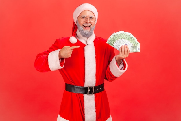 Santa claus holding fan of euro banknotes, pointing at money in his hands.