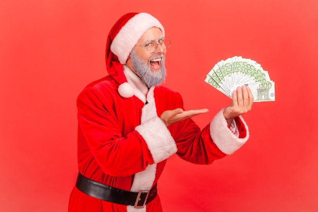 Santa claus holding fan of euro in hands, pointing at money, keeps mouth open.