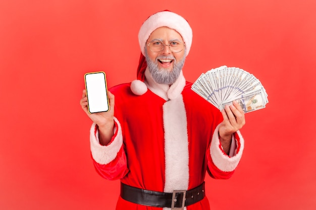 Santa claus holding fan of money and showing smartphone with white blank screen.