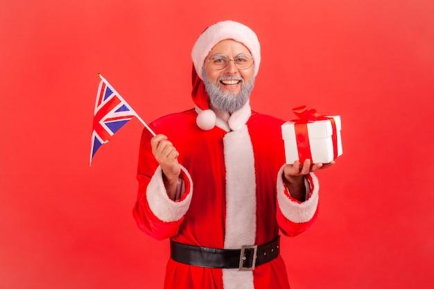 영국 국기를 들고 있는 산타클로스와 포장된 선물 상자, 크리스마스 선물.